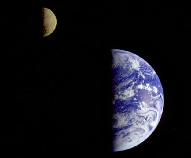 A photo taken by the Galileo spacecraft from about 6.3 million kilometers away, with Earth and moon both half-lit by the sun.